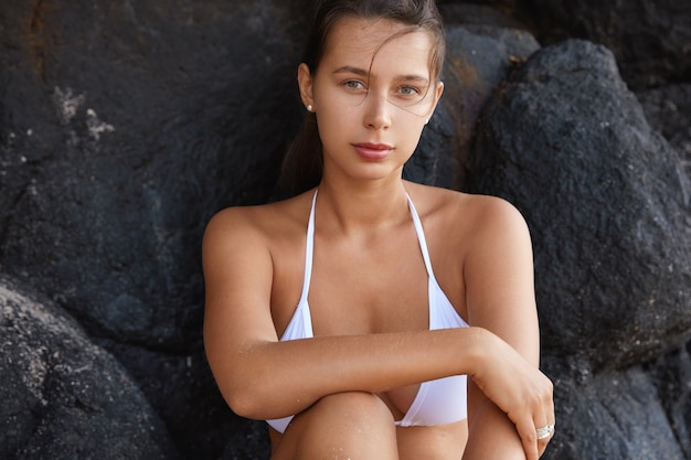 Foto horizontal de uma linda mulher em poses de biquíni branco perto de uma rocha durante o dia de verão