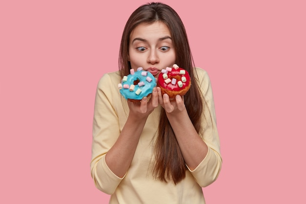 Foto horizontal de uma linda mulher europeia chocada segurando rosquinhas azuis e vermelhas, sentindo o cheiro de doces aromáticos