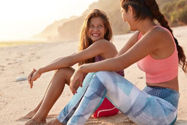 Foto horizontal de uma linda mulher europeia olhando com expressão positiva para uma namorada asiática