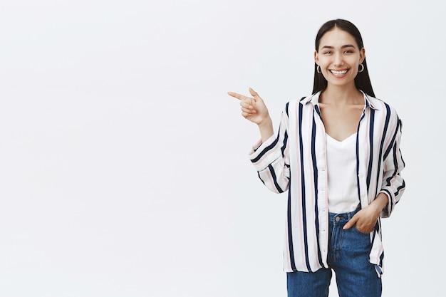 Foto horizontal de uma linda mulher feliz e otimista em jeans e blusa listrada, segurando a mão no bolso e apontando para a esquerda com o dedo indicador, sorrindo amplamente, aproveitando o momento