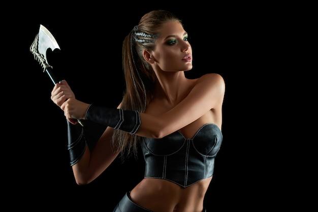 Foto horizontal de uma lutadora deslumbrante em couro, vestido de batalha da tribo amazona tradicional posando ferozmente com um machado na parede negra, protetor de guerreiro cultural histórico sexy.
