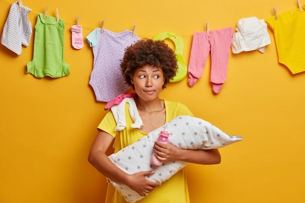 Foto horizontal de uma mãe pensativa carregando um bebê recém-nascido nos braços segurando uma garrafa de leite e desviando o olhar de poses