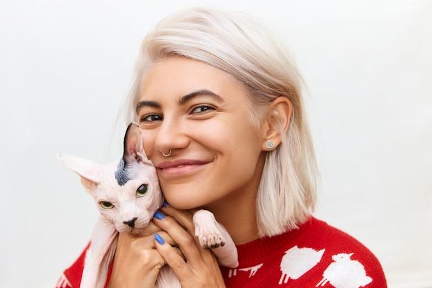 Foto horizontal de uma menina bonita sorridente com argola no nariz e penteado bob passando um tempo com seu animal de estimação, abraçando o gato sphynx cinza apertado, mostrando amor, cuidado, tendo uma expressão facial alegre e feliz