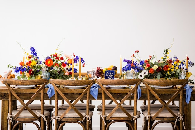Foto horizontal de uma mesa com cadeiras de madeira decorada com flores coloridas e velas