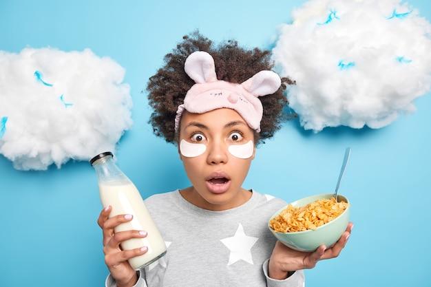 Foto horizontal de uma mulher afro-americana encaracolada e chocada encara os olhos esbugalhados para a câmera, come um café da manhã saudável e reage a notícias incríveis vestida de pijama isolado sobre a parede azul