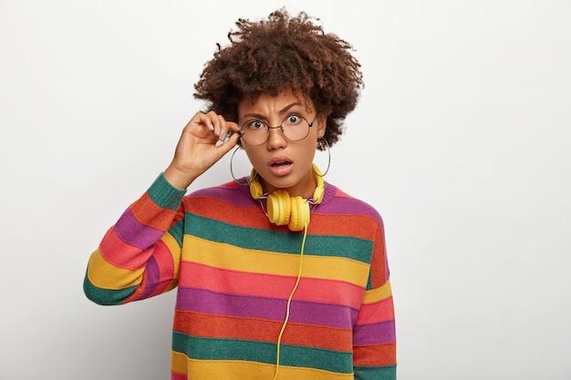 Foto horizontal de uma mulher afro-americana encaracolada e perplexa tocando a armação dos óculos, parece surpreendente, ouve algo incrível, usa um macacão listrado multicolorido
