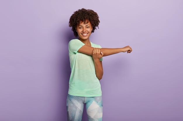 Foto horizontal de uma mulher afro-americana feliz e esportiva estende as mãos antes do treino, sorri feliz, vestida com roupa ativa e tem corpo flexível