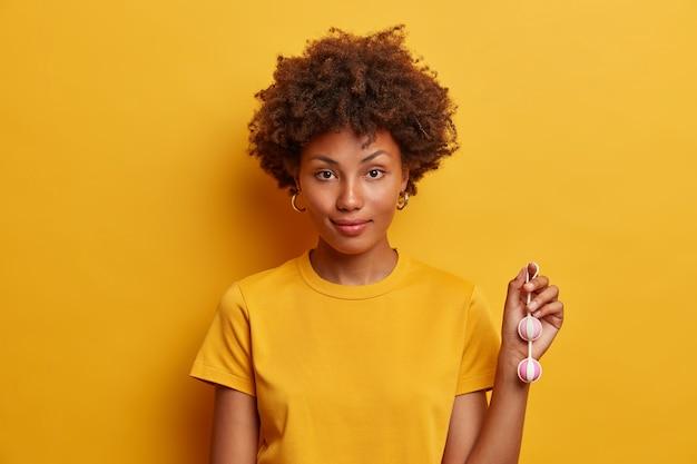 Foto horizontal de uma mulher afro-americana usando bolas de kegel na corda para impulsionar a vida sexual, realiza exercícios regulares para fortalecer os músculos pélvicos da vagina, aumenta a sensação sexual antes do sexo com penetração