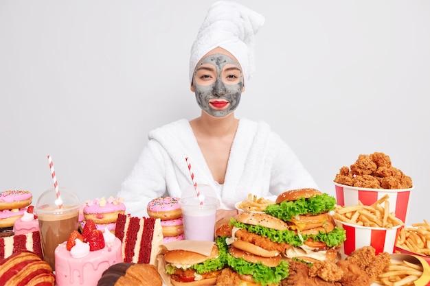 Foto horizontal de uma mulher asiática confiante cercada por junk food