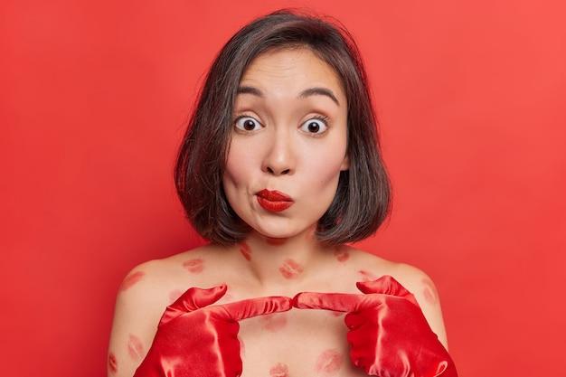 Foto horizontal de uma mulher asiática hesitante e sem noção com o mínimo de maquiagem, batom vermelho se sente hesitante e desatenta, usa luvas nas mãos, tem vestígios de lábios no corpo, poses internas