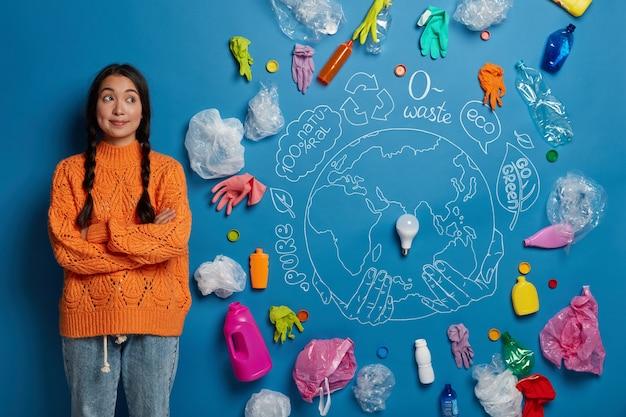 Foto horizontal de uma mulher asiática pensativa com as mãos cruzadas, recolhendo o lixo e pensando sobre os problemas ecológicos