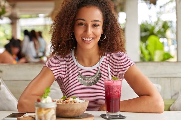 Foto horizontal de uma mulher bonita com expressão facial satisfeita