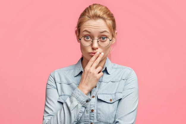 Foto horizontal de uma mulher bonita de cabelos claros com perplexidade diretamente para a câmera, usa óculos redondos, mantém os dedos nos lábios, focalizou o olhar e o interlocutor escuta atentamente as informações