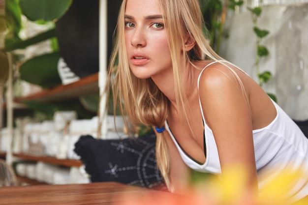 Foto horizontal de uma mulher bonita vestida com um top, senta-se perto da mesa, espera o pedido no restaurante, pensa em algo importante, passa as férias de verão em boa companhia.