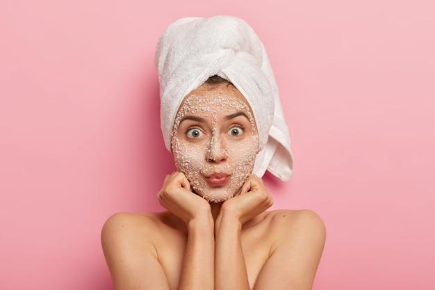 Foto horizontal de uma mulher caucasiana surpresa mantém as palmas das mãos sob o queixo, olha com os olhos arregalados, aplica máscara esfoliante, evita problemas de pele, fica sem camisa contra a parede rosa. conceito de beleza