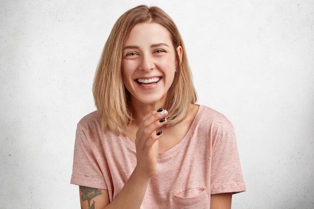 Foto horizontal de uma mulher de aparência agradável rindo de uma boa piada, alegre, tem um sorriso largo, vestida casualmente, faz manicure, isolada sobre concreto branco