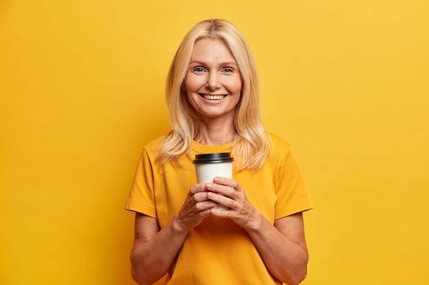 Foto horizontal de uma mulher de meia-idade bem enrugada segurando uma xícara descartável de café, aproveitando o tempo livre e olhando feliz para a câmera vestida com uma camiseta casual