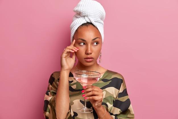 Foto horizontal de uma mulher de pele escura pensativa, concentrada ao lado, pensativa, tomando coquetéis de pele bem cuidada