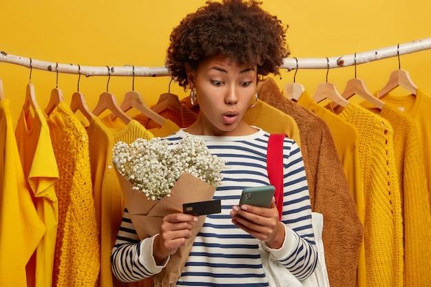 Foto horizontal de uma mulher encaracolada surpresa usando um celular moderno, verificando o saldo, segurando o cartão de crédito, fazendo compras online