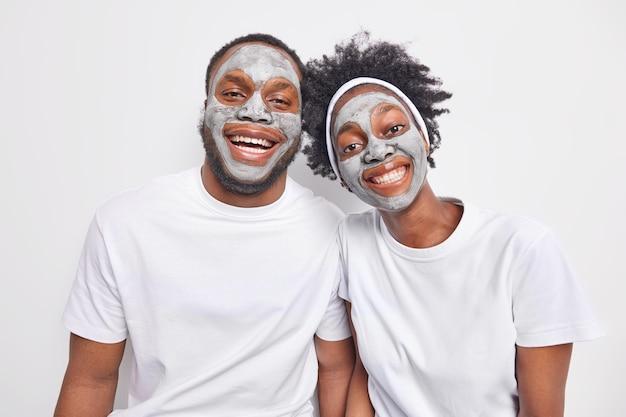 Foto horizontal de uma mulher étnica amigável e um homem perto um do outro, sorrindo amplamente, mostrando os dentes brancos, cuidando da pele, use uma máscara de beleza nutritiva para uma pele saudável, tenham boas relações