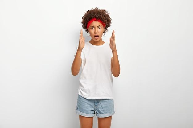 Foto horizontal de uma mulher étnica encaracolada impressionada medindo com as duas mãos, mostrando sinais grandes e grandes
