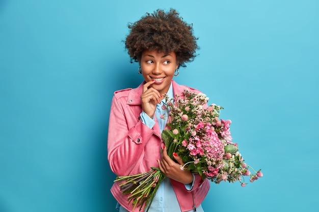 Foto horizontal de uma mulher étnica sonhadora olhando alegremente para o lado segurando um buquê de flores