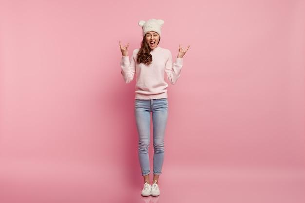 Foto horizontal de uma mulher européia encaracolada e feliz fazendo um gesto de rock n roll, exclama positivamente, estando em alto astral, usa capacete