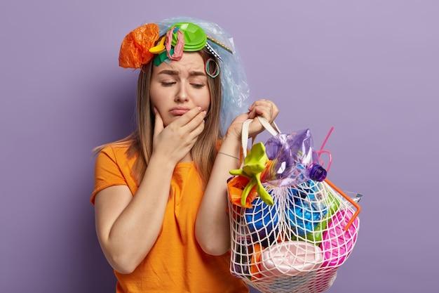 Foto horizontal de uma mulher europeia insatisfeita com expressão facial triste, segura um saco de resíduos de polietileno, segura o queixo, deprimida com o meio ambiente destruído e sério problema de poluição