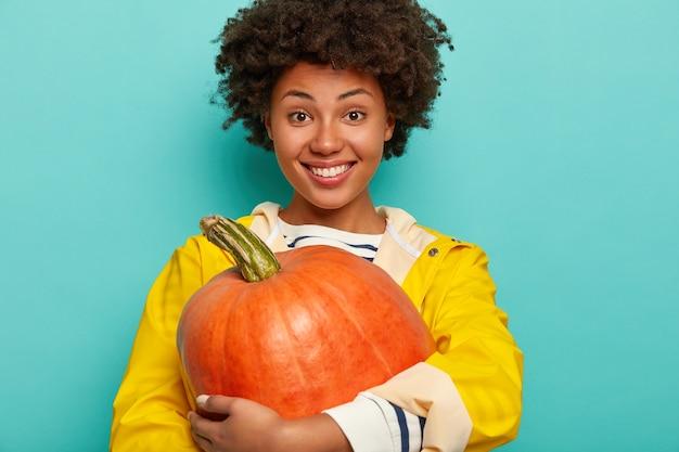 Foto horizontal de uma mulher feliz de pele escura segurando vegetais maduros de outono, abraçando uma grande abóbora, tem um sorriso cheio de dentes e usa uma capa de chuva amarela