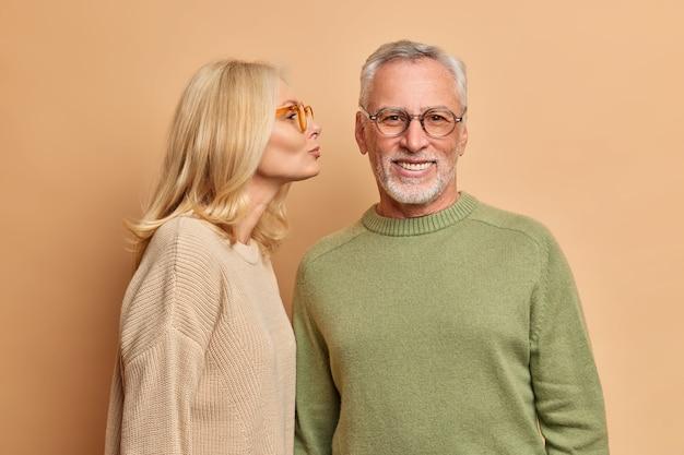 Foto horizontal de uma mulher idosa loira carinhosa beija o marido na bochecha e expressa afeto e sentimentos ternos