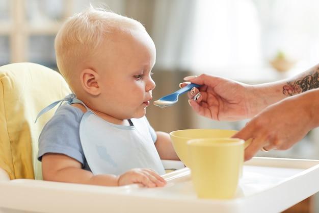 Foto horizontal de uma mulher irreconhecível alimentando seu filho bebê com comida sólida