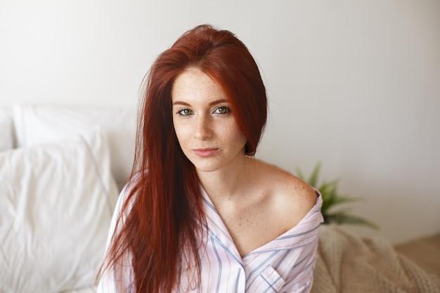 Foto horizontal de uma mulher jovem e bonita com cabelo ruivo e sardas sentada na roupa de cama branca com aparência de sono porque ela não dormiu o suficiente à noite. conceito de manhã, cama e estilo de vida