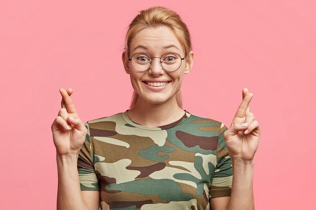 Foto horizontal de uma mulher loira bonita em uma camiseta militar casual, mantém os dedos cruzados na esperança de realizar os sonhos, tem expressão positiva, isolado sobre o rosa