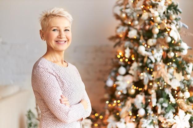 Foto horizontal de uma mulher madura de cabelos curtos elegante e atraente em clima festivo, celebrando o natal, posando em uma árvore decorada com brinquedos e guirlandas, mantendo os braços cruzados sobre o peito, sorrindo