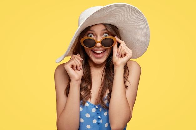 Foto horizontal de uma mulher muito atraente com cabelo escuro, parece com surpresa e felicidade, mantém a mão na borda dos tons, modelos com roupa de verão sobre parede amarela. conceito de beleza e emoções