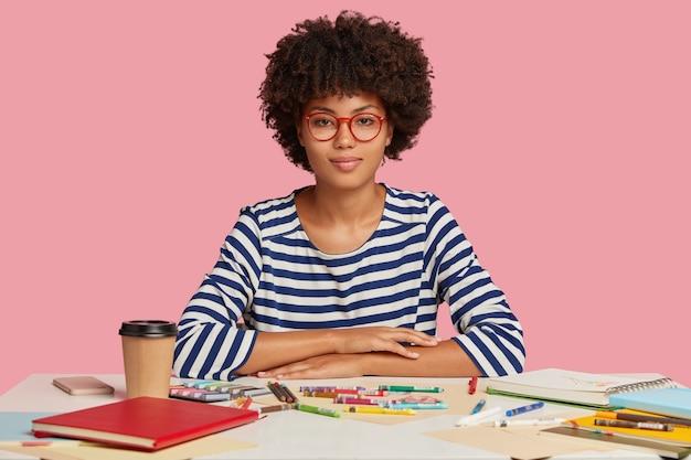 Foto horizontal de uma mulher negra atraente com cabelo crespo, com expressão séria, sentada na mesa branca, fazendo ilustrações em um caderno espiral, vestida com um macacão casual listrado, óculos ópticos