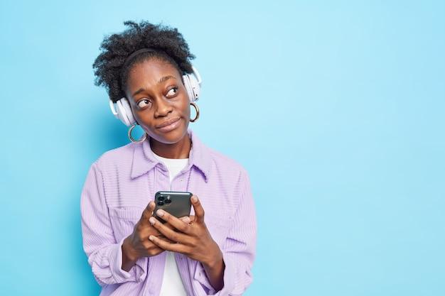 Foto horizontal de uma mulher pensativa de pele escura com cabelo encaracolado pensando em planos para o futuro