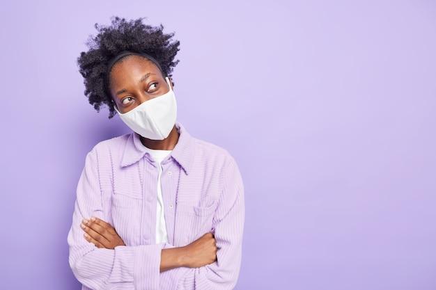 Foto horizontal de uma mulher pensativa de pele escura usando máscara descartável como proteção contra o coronavírus
