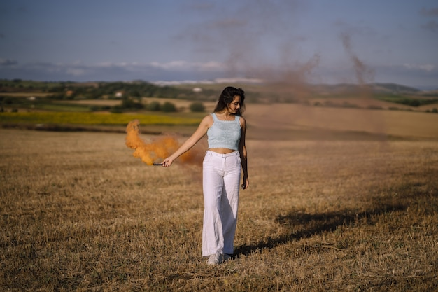 Foto horizontal de uma mulher posando com uma bomba de fumaça no campo