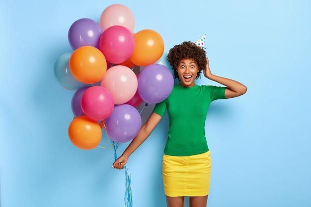 Foto horizontal de uma mulher radiante segurando balões multicoloridos enquanto posa com um chapéu de aniversário