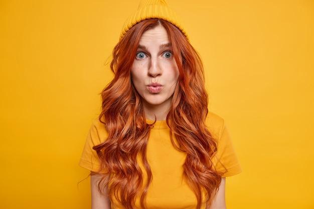 Foto horizontal de uma mulher ruiva impressionada parece maravilhada, mantém os lábios dobrados