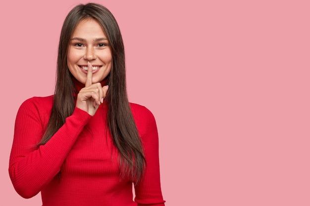 Foto horizontal de uma mulher sorridente satisfeita mantendo o dedo indicador sobre os lábios, mostrando um gesto silencioso