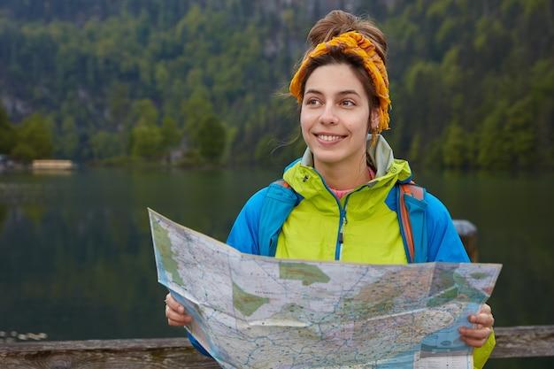 Foto horizontal de uma mulher viajante ativa e alegre segurando um mapa turístico