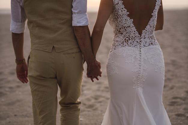 Foto horizontal de uma noiva e uma vassoura segurando as mãos uma da outra na praia