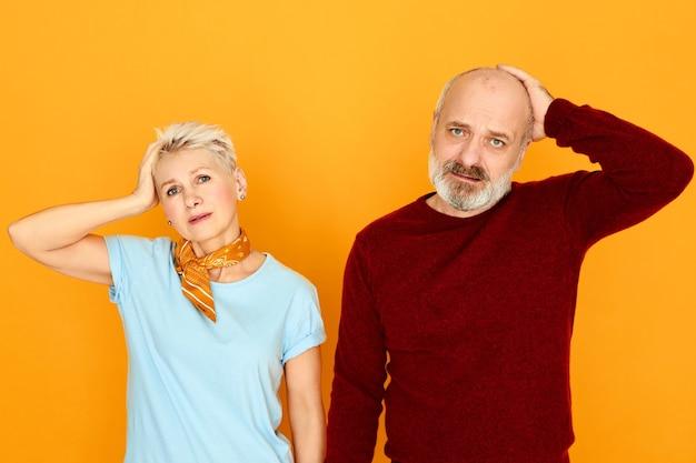 Foto horizontal de uma senhora caucasiana de meia-idade esquecida emocionalmente e seu marido idoso careca com a barba por fazer expressando verdadeira reação de surpresa, segurando as mãos na cabeça, tendo um olhar confuso e sem noção