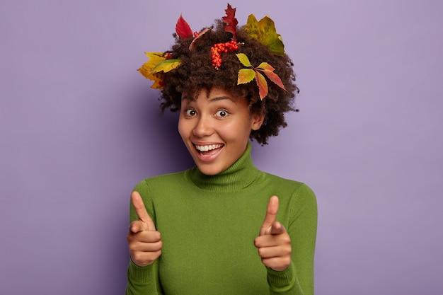 Foto horizontal de uma senhora sorridente com uma expressão feliz, aponta o dedo para a câmera e usa um casaco verde