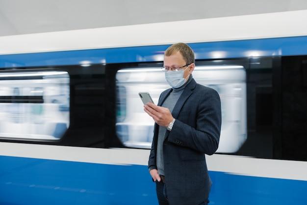 Foto horizontal de viajante masculino usa transporte público para se deslocar, usa máscara médica para se proteger de coronavírus ou covid-19, aguarda trem, usa telefone celular, envia mensagens de texto no bate-papo
