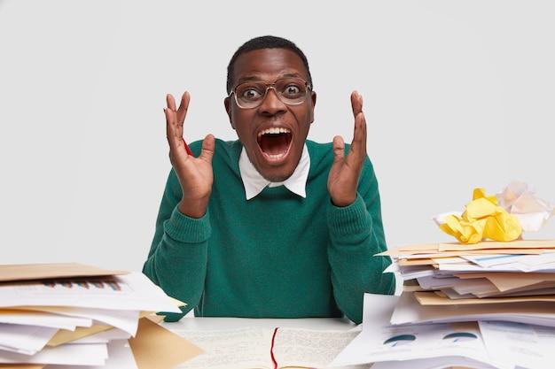 Foto horizontal do financista emocional, gesticula com as mãos, abre a boca amplamente