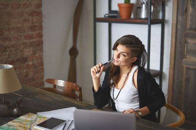 Foto horizontal interna de uma mulher jovem e bonita com um corte de cabelo estiloso, trabalhando em um escritório em casa, sentado em frente a um laptop genérico, olhando pensativo, sonhando com férias à beira-mar