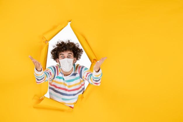 Foto humana de jovem macho com máscara estéril no piso amarelo cor de saúde covid pandemia de vírus